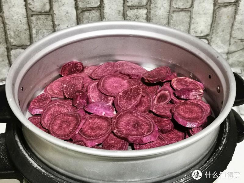 把紫薯外皮的泥沙洗干净,用刮刀刮掉外皮,切掉头尾,再切成薄片,摆放在蒸屉上,水开后再蒸10分钟;